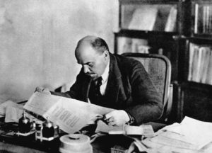 ca. 1918-1923, Moscow, Russia --- Lenin sits at his desk and reads the newspaper. --- Image by © CORBIS